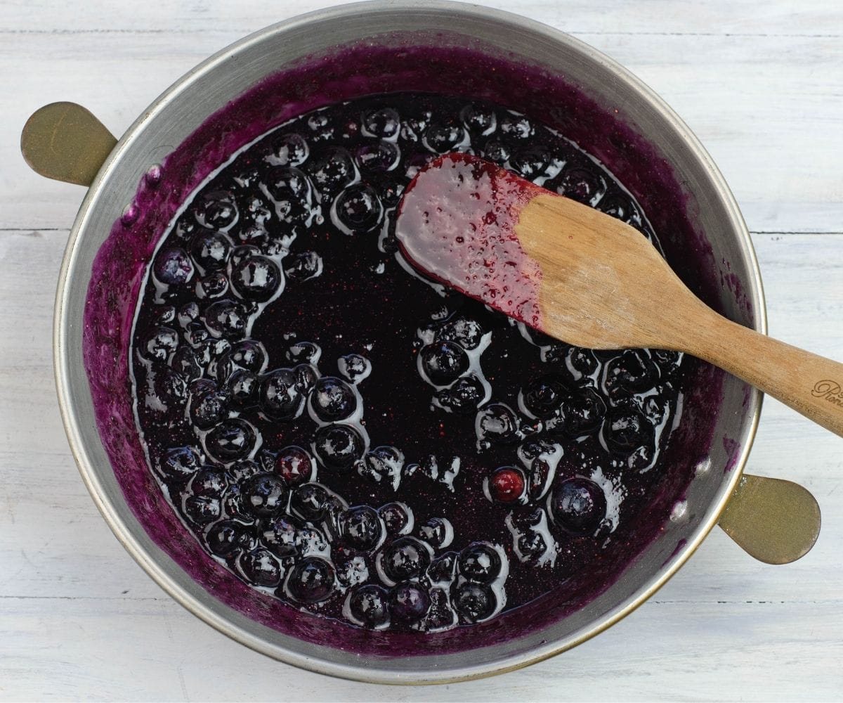 Cooking homemade blueberry pancake syrup in a cooper pot.