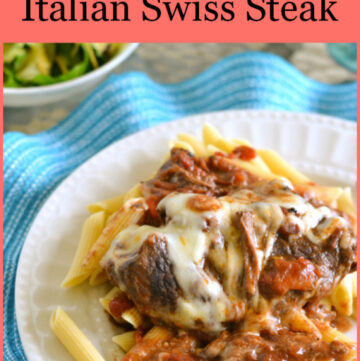 A serving of Crock Pot Swiss Steak served over a bed of pasta