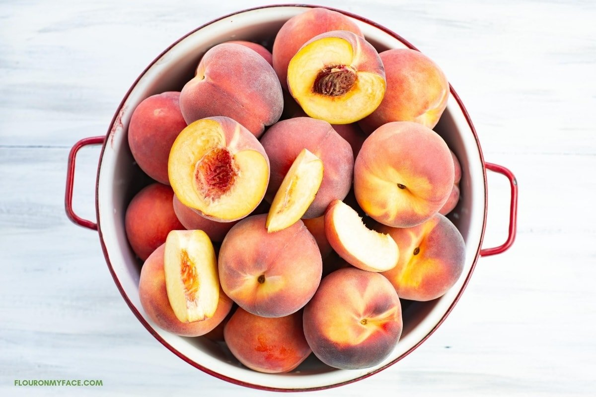 fresh whole and sliced peaches in a white enamel colander