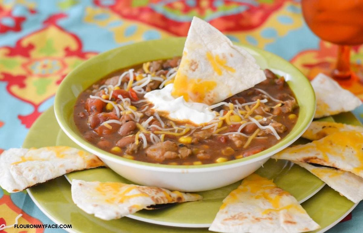 Sausage Chili in a bowl topped with sour cream.
