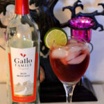 Red Moscato Cocktail in a wine glass with lime wedge for Halloween