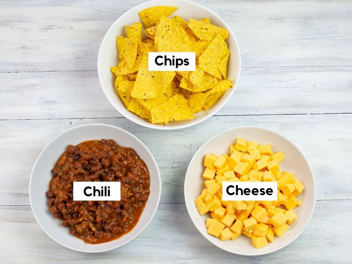 Cubed Velveeta cheese, chili with beans and corn chips Cheese dip ingredients in individual bowls.