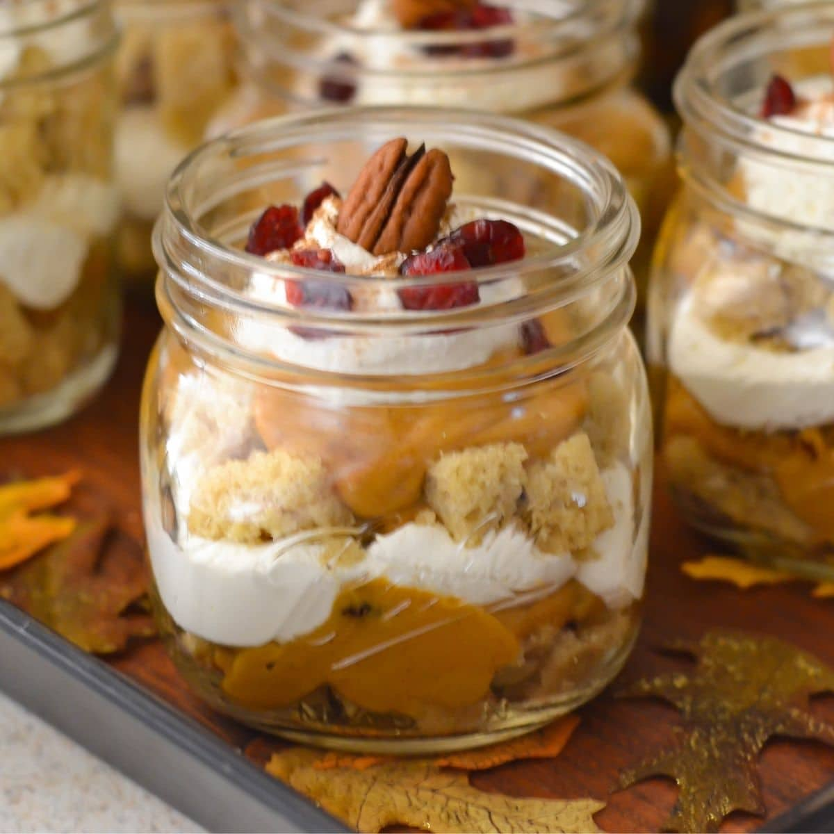Pumpkin Cranberry Trifle served in a mason jar on a serving tray.