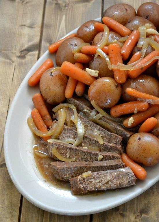 Crock Pot London Broil on serving platter with potatoes and carrots
