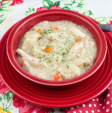 a red bowl filled with thick and creamy easy Crock Pot Chicken and Dumplings made with canned biscuits.