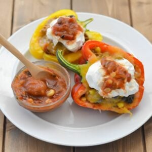 Stuffed bell peppers on a plate topped with sour cream and salsa.