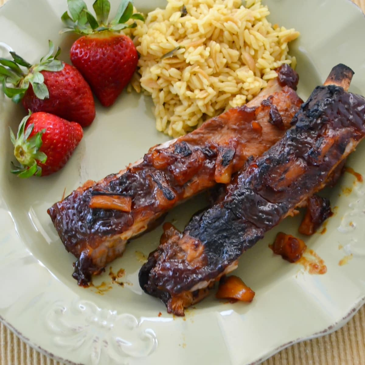 Hawaiian style BBQ Pork Ribs served on a green plate with fresh strawberries and yellow rice.