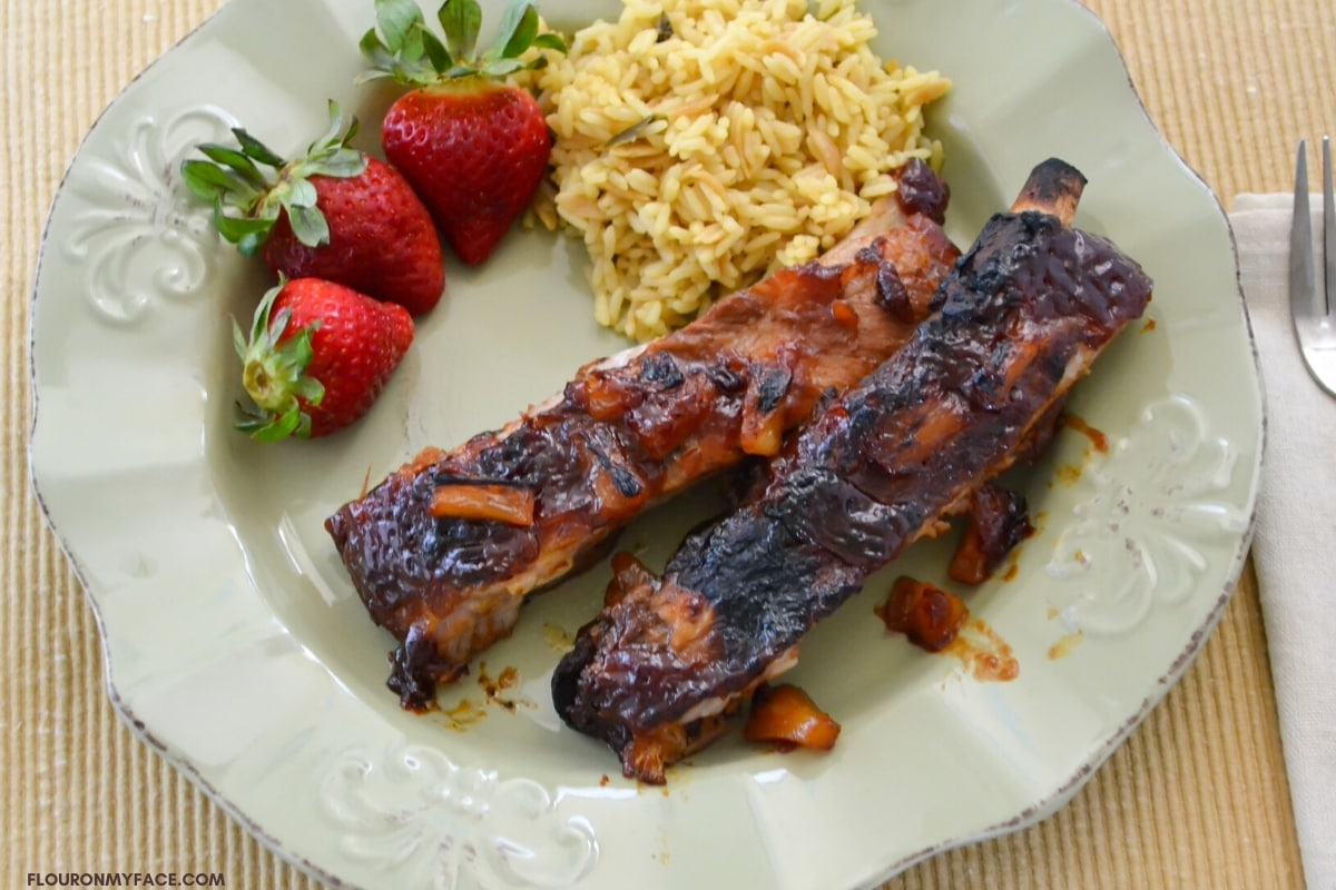 Hawaiian style pork spare ribs with pineapple served on a plate with fresh berries and yellow rice