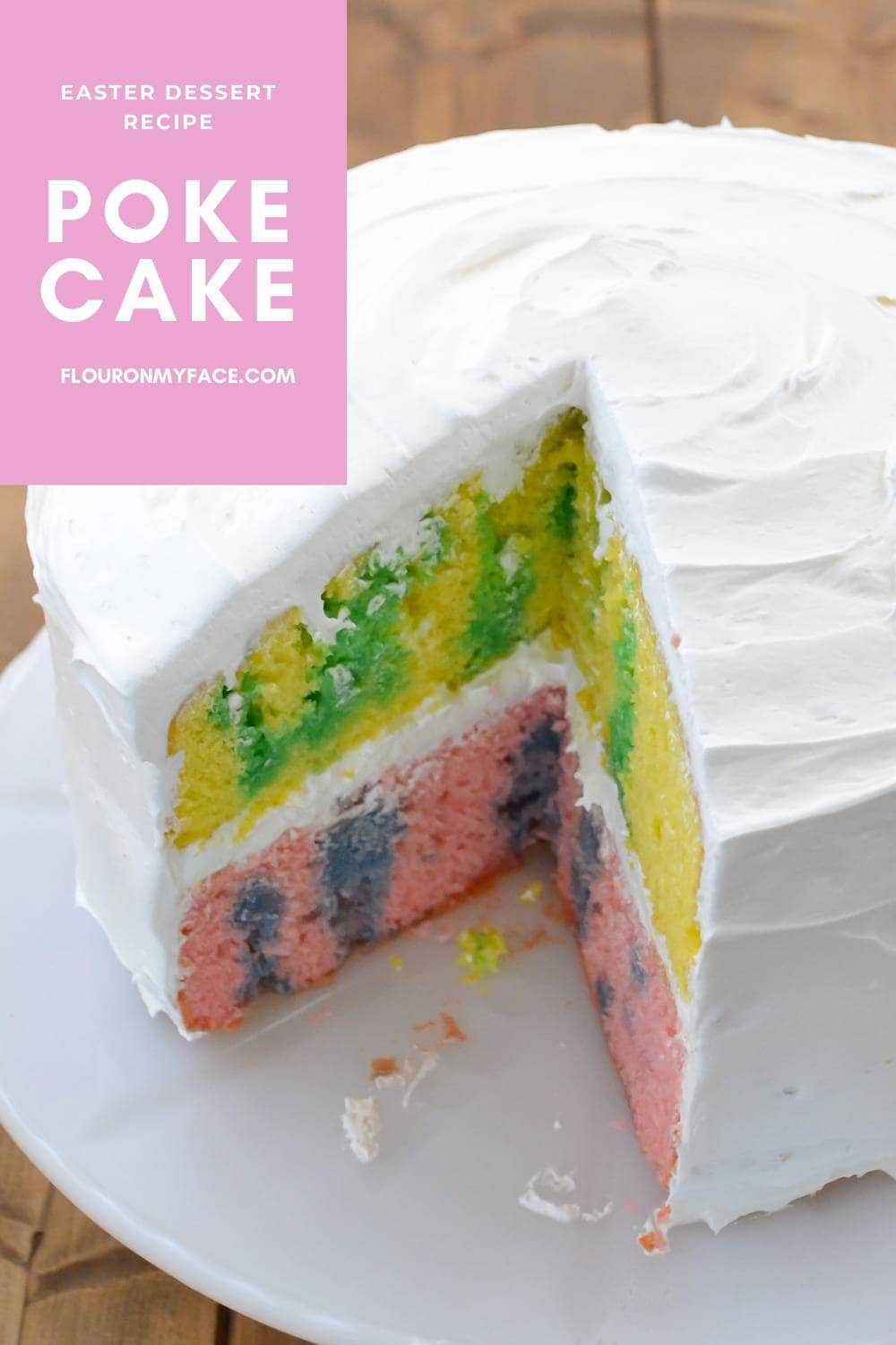 A colorful Easter cake served on a cake plate with one wedge cut out.