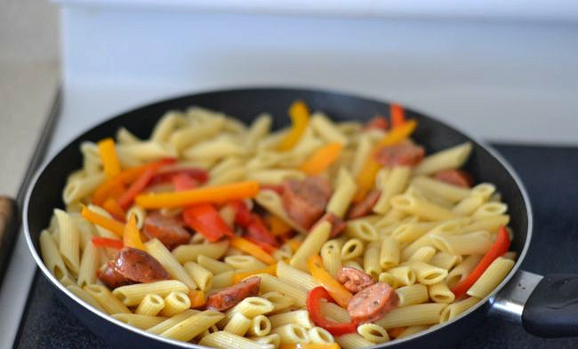 Adding cooked pasta to the skillet for an easy skillet pasta recipe via flouronmyface.com