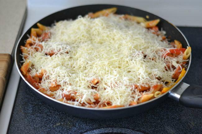 Adding mozzarella cheese to the skillet for this easy Pasta skillet recipe via flouronmyface.com