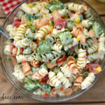 Pasta salad with tri colored noodles and garden vegetables in a large serving bowl.
