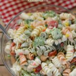 A serving bowl filled with tri colored Broccoli Tomato Pasta Salad.