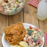 Pasta salad served with fried chicken and chips.
