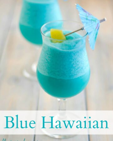 Frozen Blue Hawaiian Cocktail served in a hurricane glass with a blue paper umbrella and chunk of pineapple