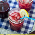 Blackberry Iced Tea in a glass with lemon wedge.