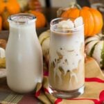 A small bottle of homemade Pumpkin Spice Coffee Creamer next to a glass of iced coffee.