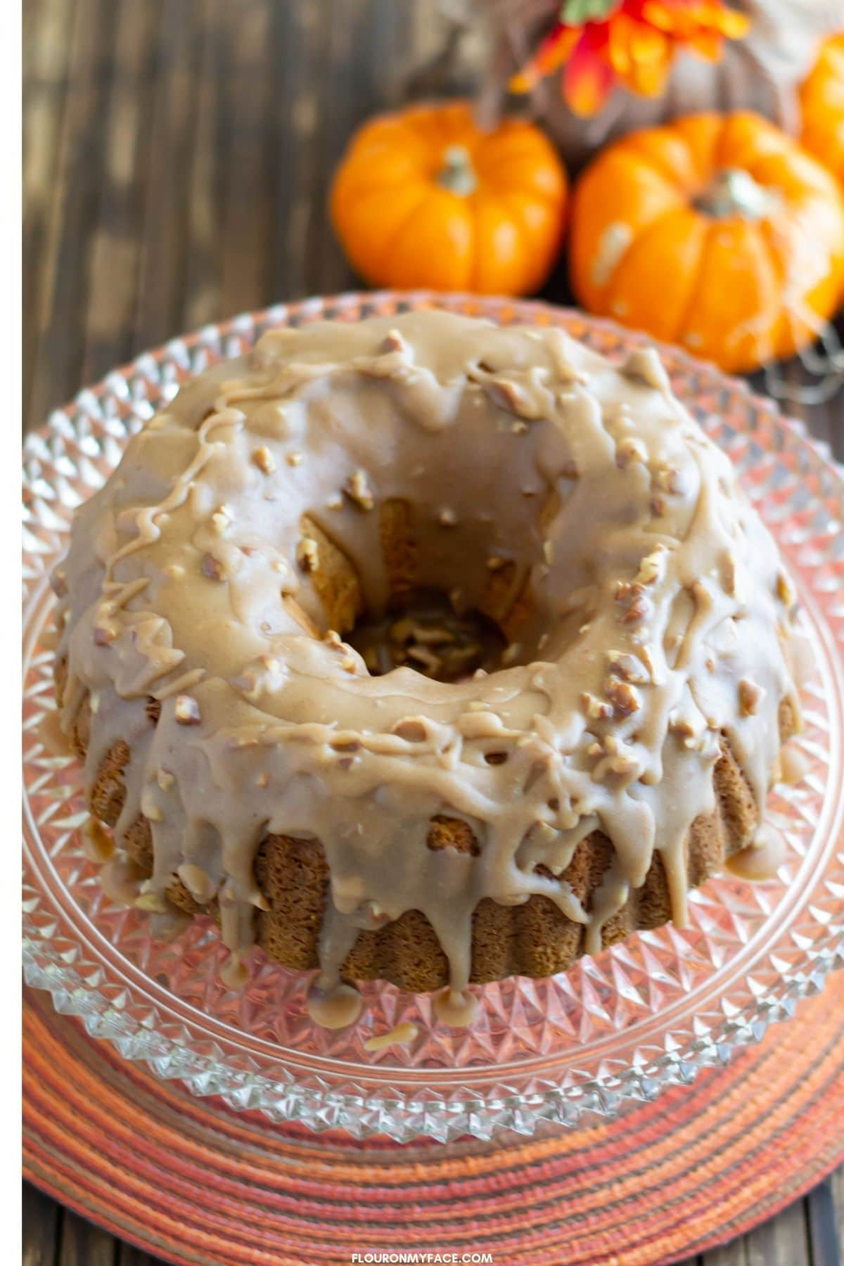 A pecan spice bundt cake on a glass cake stand before cutting.