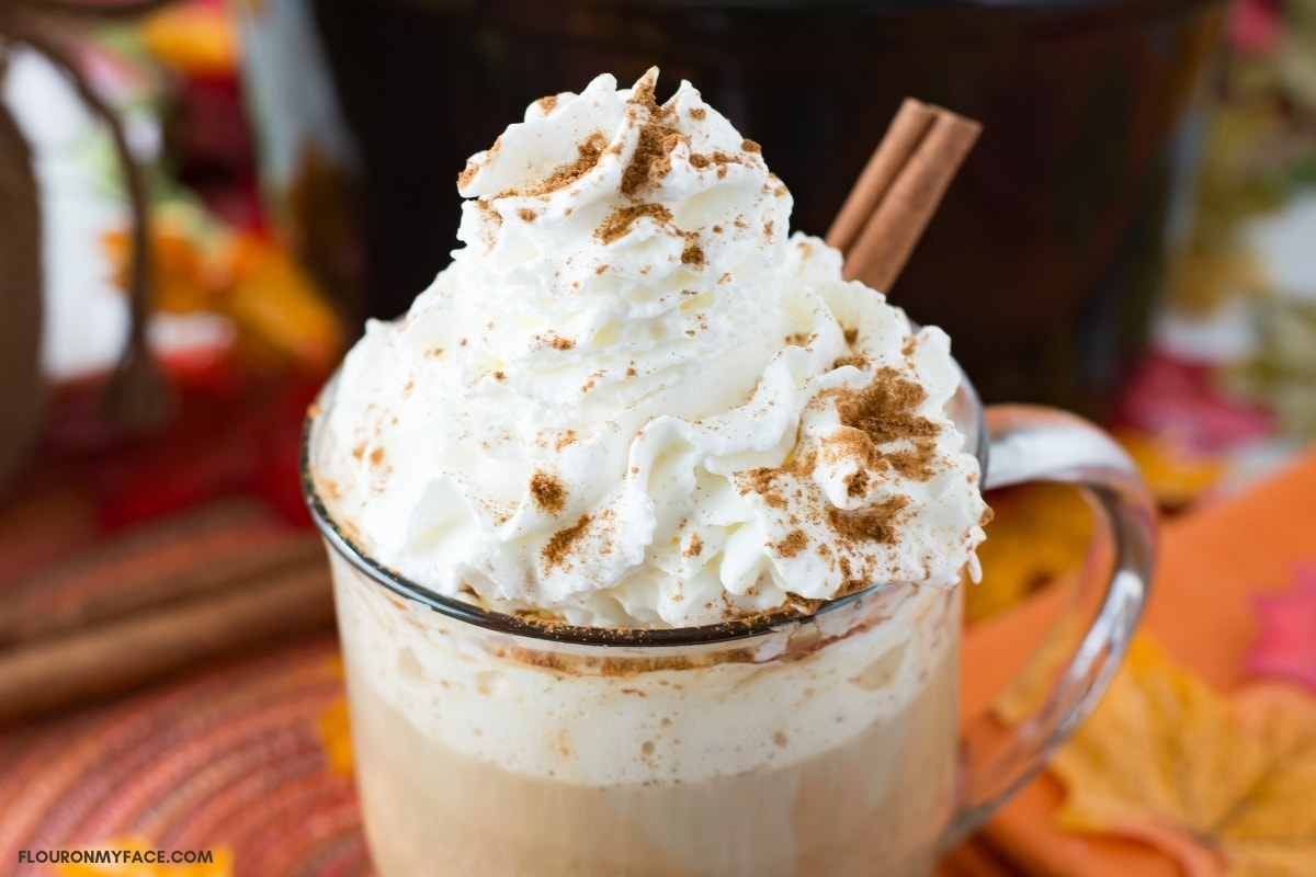 A mug filled with pumpkin spice rumcahatta latter, topped with whipped cream and sprinkled with pumpkin spice seasoning