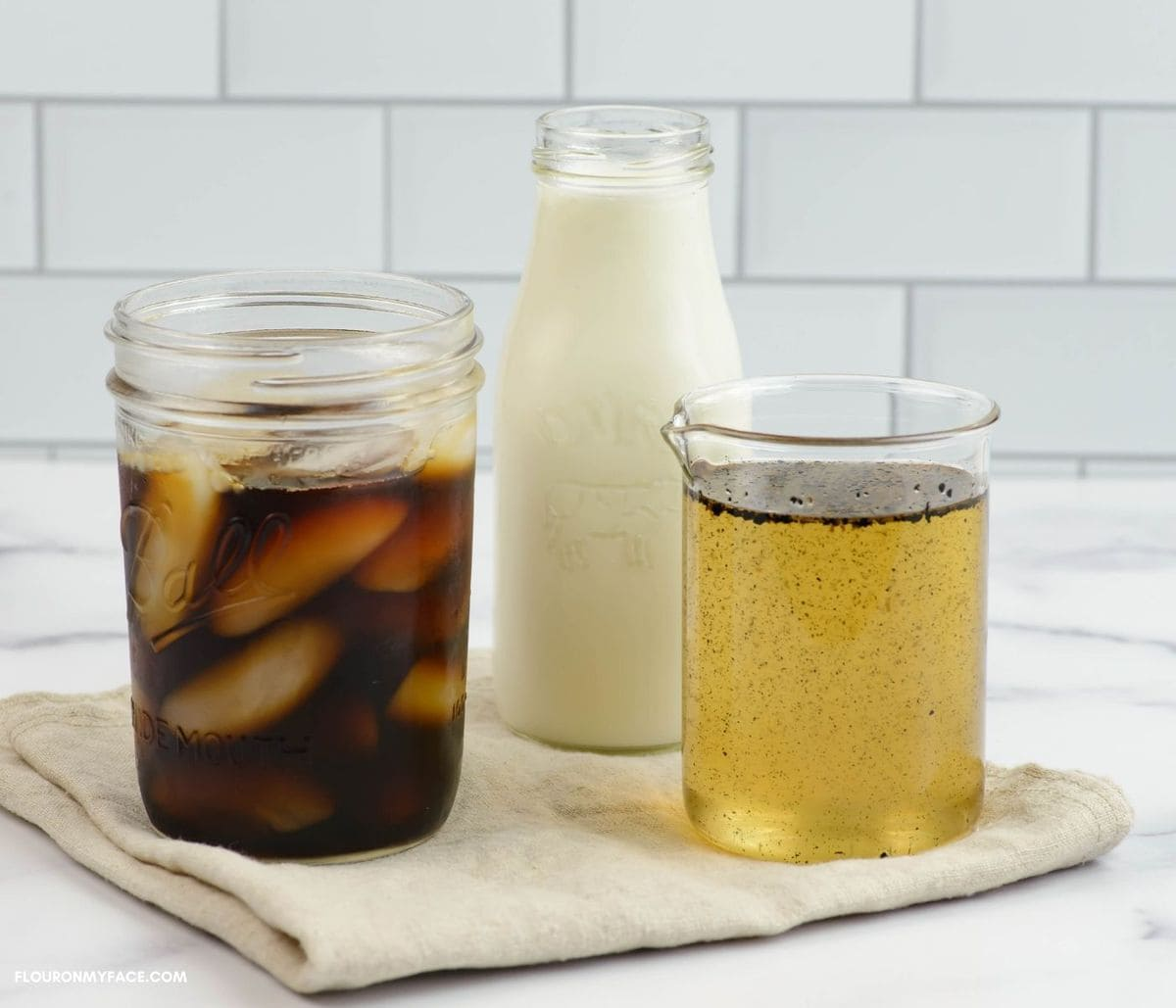 Vanilla syrup, glass of iced coffee and a small bottle filled with milk.