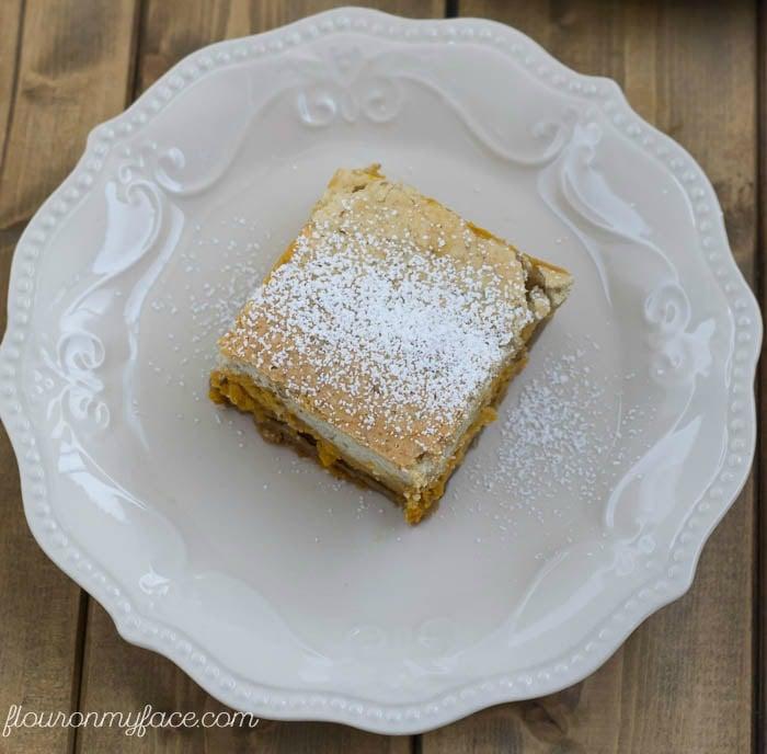 Pumpkin Cheesecake Bars recipe is a perfect fall dessert recipe combining pumpkin with a cheesecake filling via flouronmyface.com