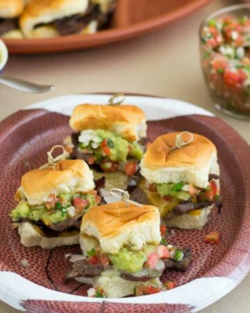 A plate with carne asada sliders.