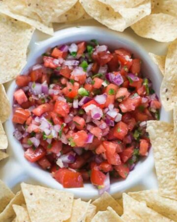 Homemade Pico de Galo in a dip bowl surrounded by chips.