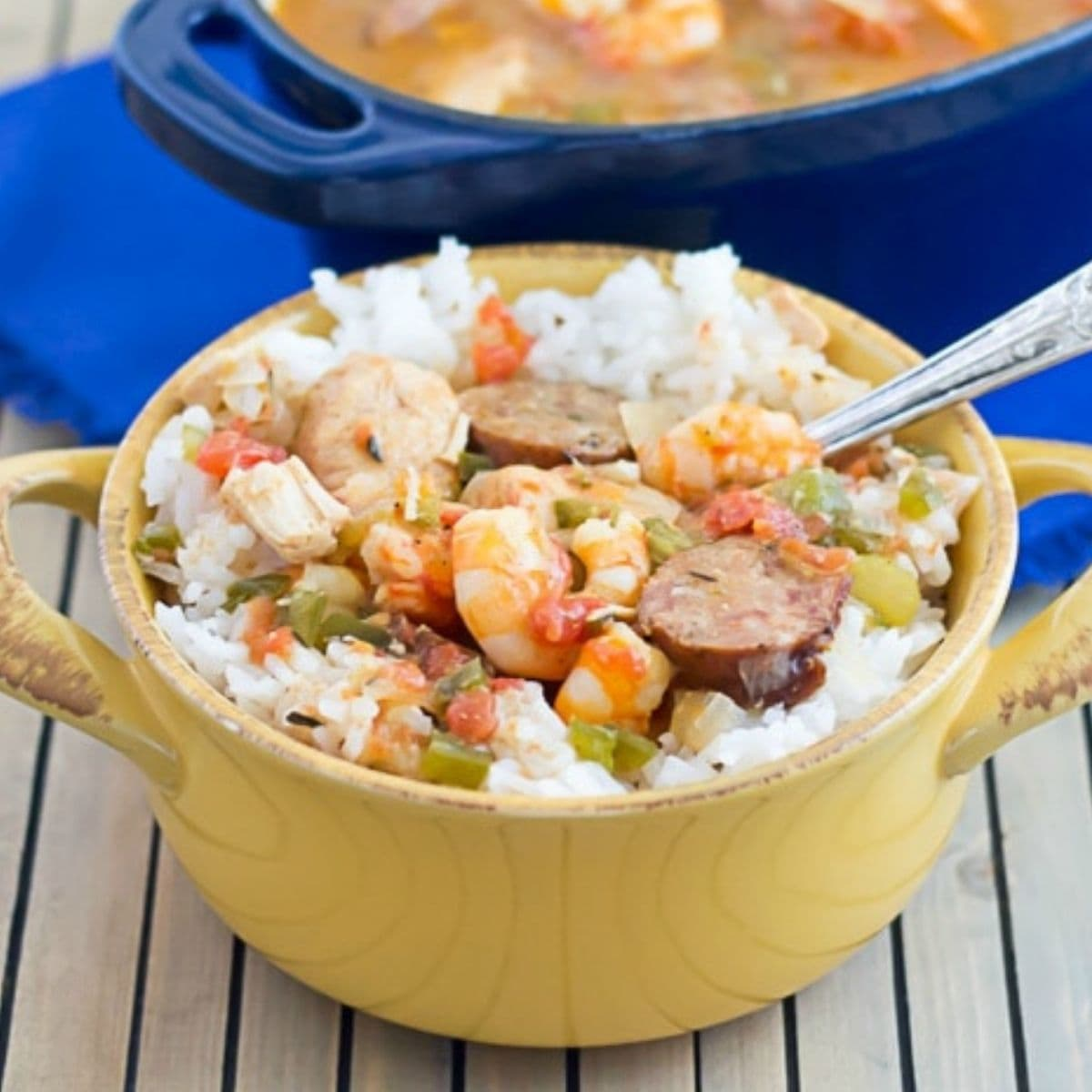 A yellow soup crock filled with white rice topped with Creole Jambalaya.