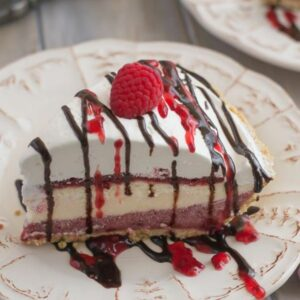 A slice of raspberry cheesecake pudding pie on a dessert plate.