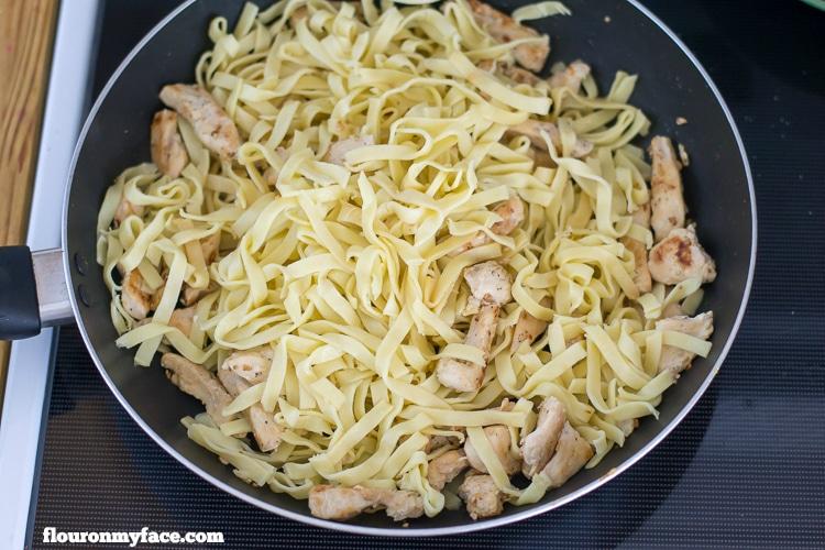 Adding fresh pasta to the pan for chicken alfredo AD via flouronmyface.com