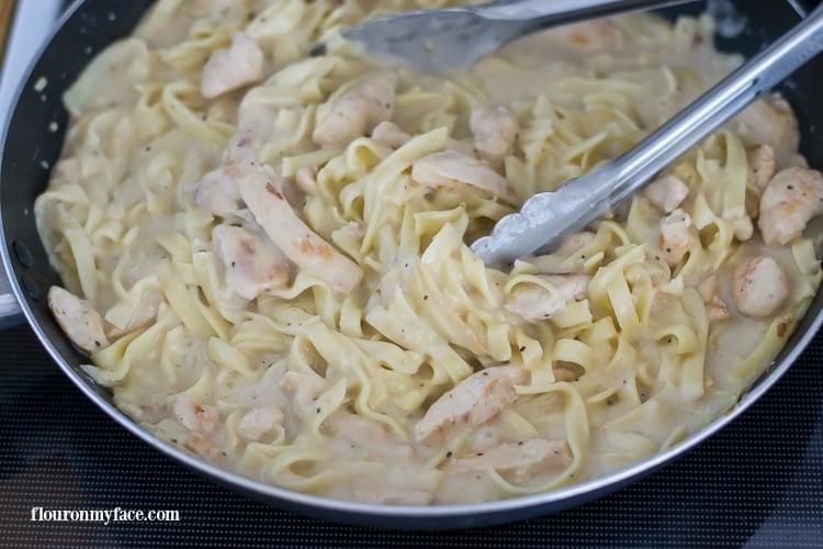Adding the Tyson® Meal Kit Alfredo Sauce to the pan via flouronmyface.com AD