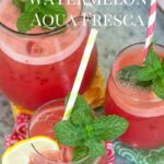 Glass pitcher with glasses filled with Watermelon Aqua Fresca.