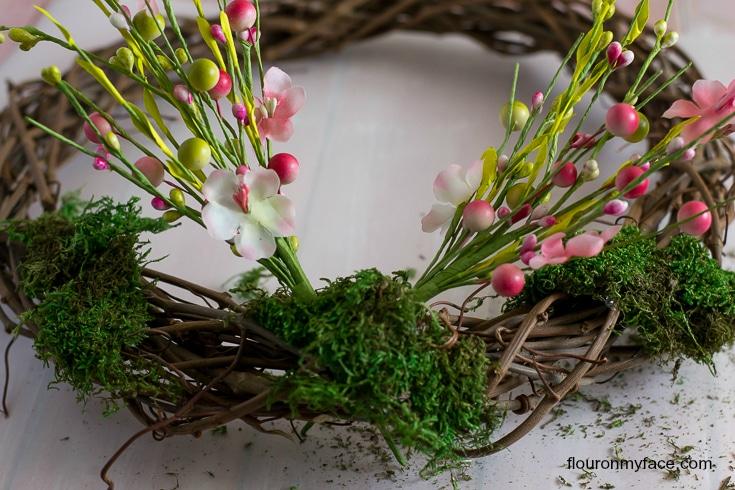 Attaching floral picks to a grape vine wreath via flouronmyface.com