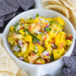 close up photo of mango peach salsa in a dip bowl with white and purple tortilla chips