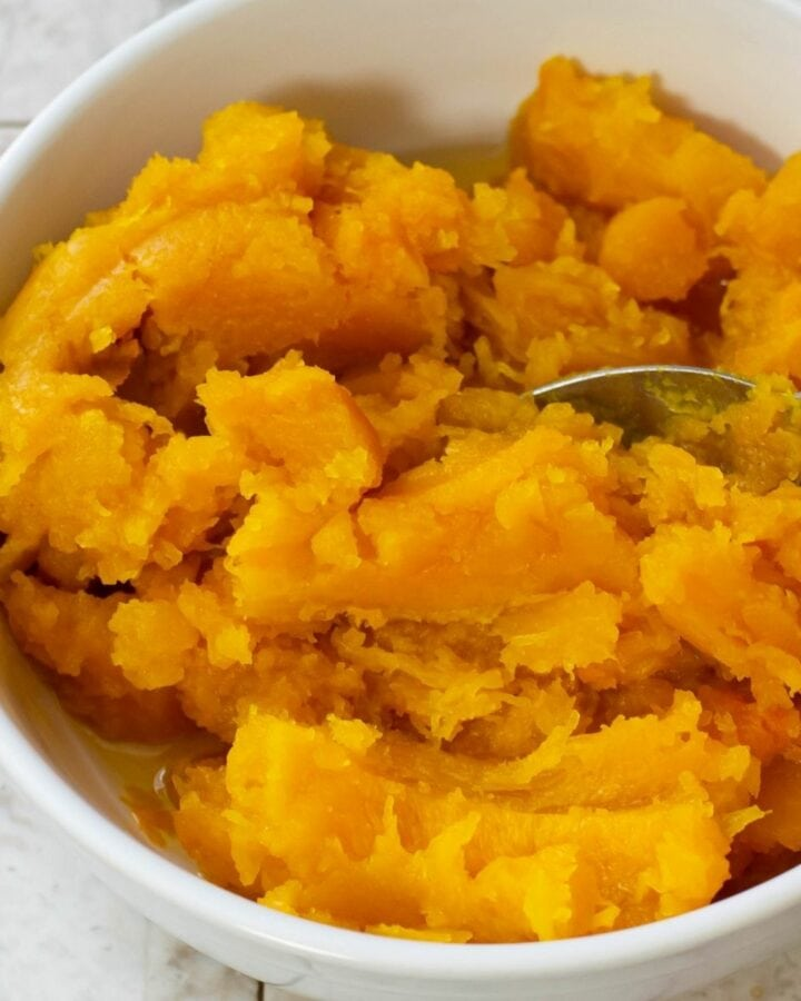 A white bowl filled with homemade pumpkin puree.
