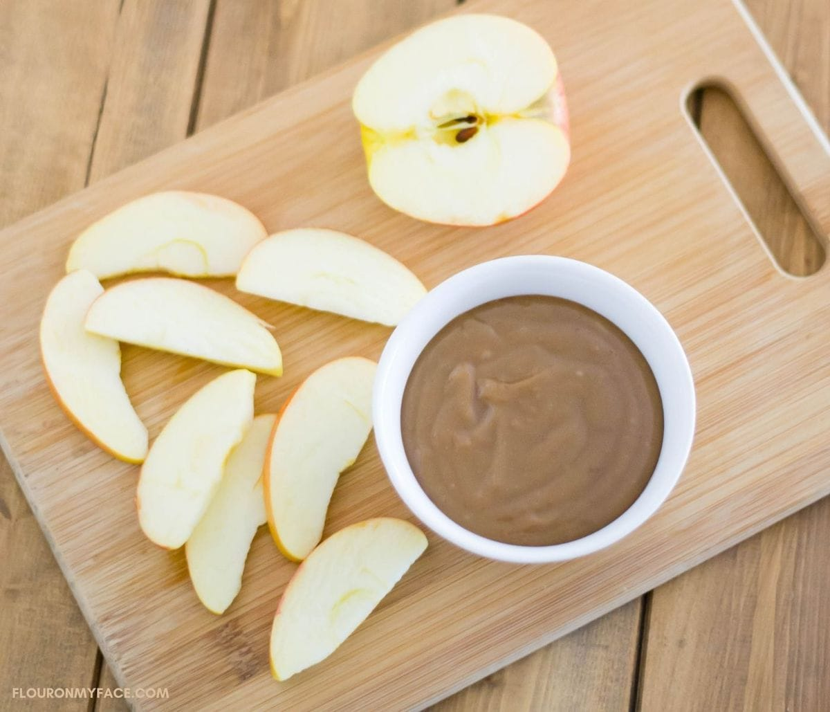 A sliced apple on a cutting board next to a bowl filled with caramel dip.