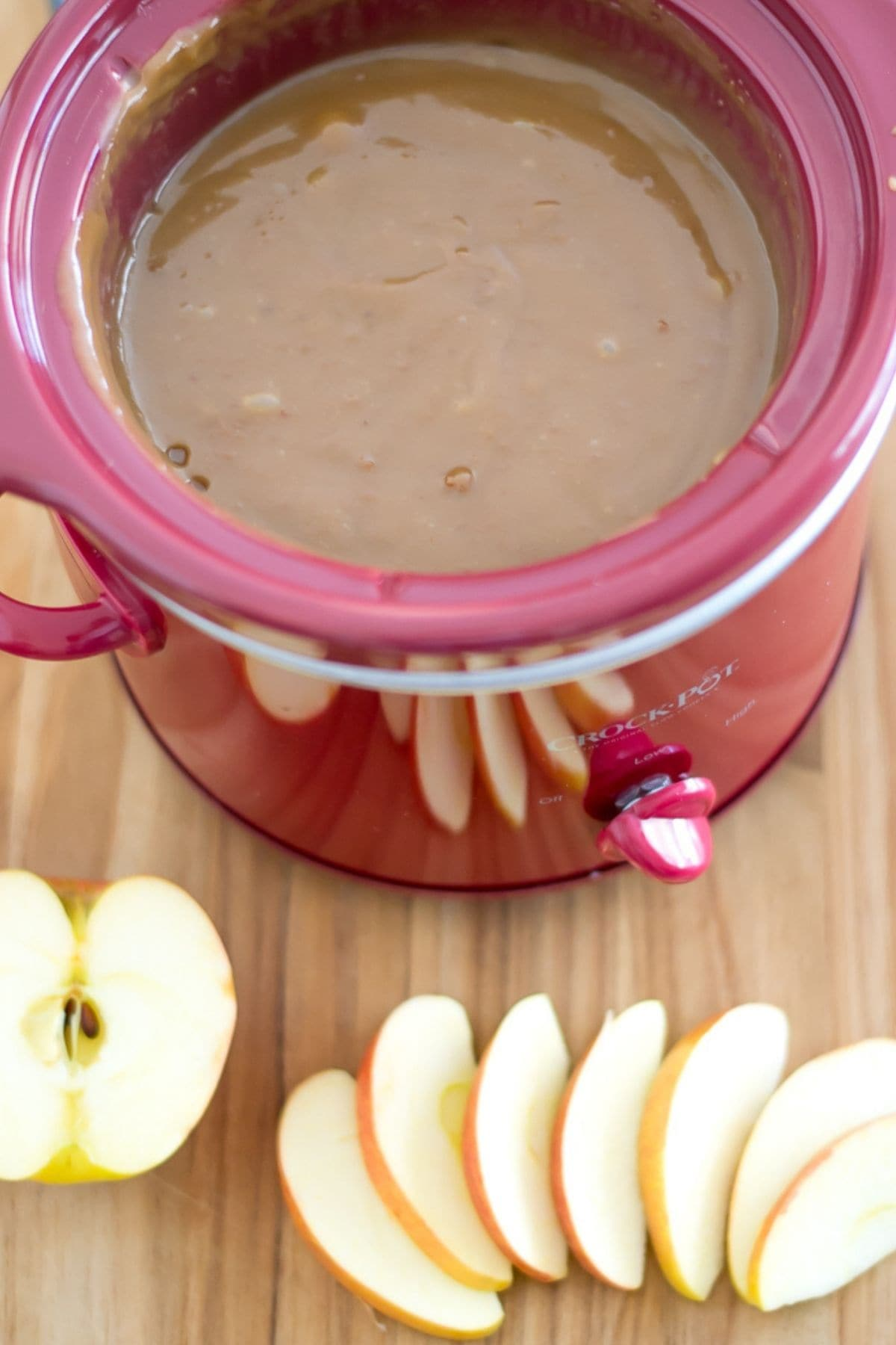 Overhead photo of a small crock pot filled with caramel dip and sliced apples on a cutting board.
