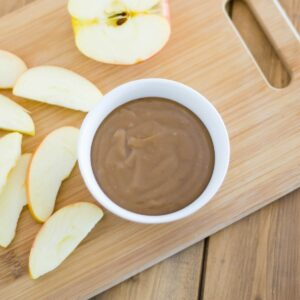 A small bowl of caramel dip with sliced apples on a cutting board.