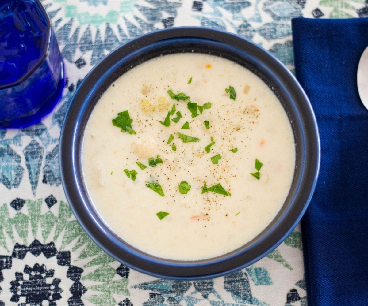 A dark blue bowl filled with a thick and creamy cauliflower soup recipe.