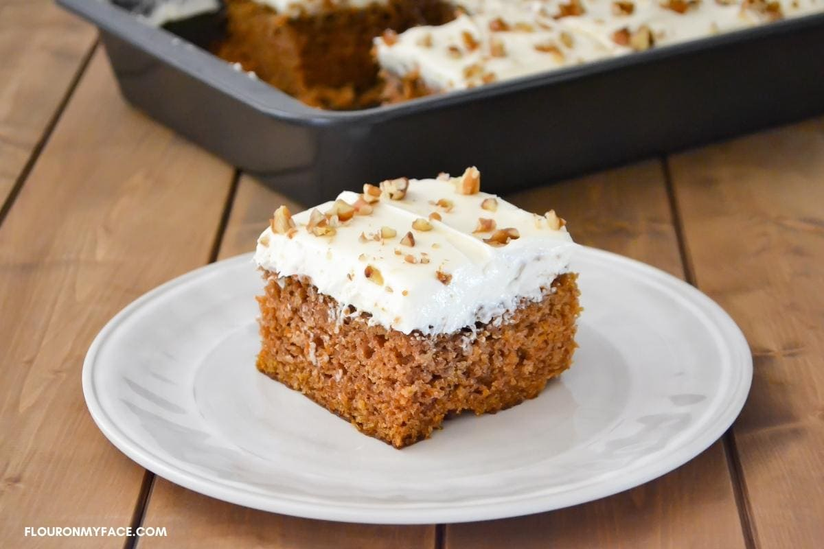 A square piece of carrot cake on a dessert plate.