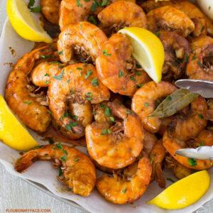 New Orleans Style BBQ Shrimp piled on a serving platter with lemon wedges