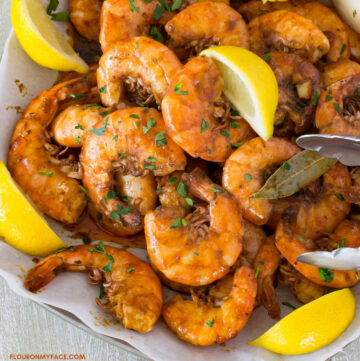 New Orleans Style BBQ Shrimp piled on a serving platter with lemon wedges