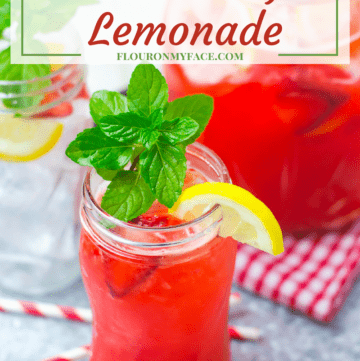 Strawberry Lemonade in a tall mason jar with sliced lemon and fresh mint with a full pitcher behind it on a serving tray