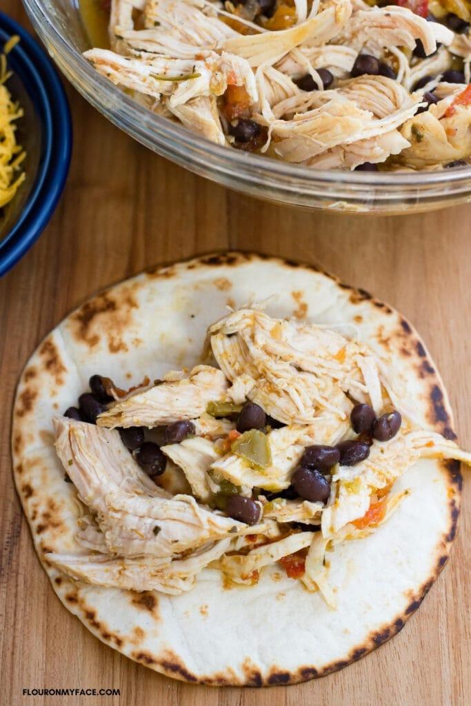 chicken taco filling on a flour tortilla