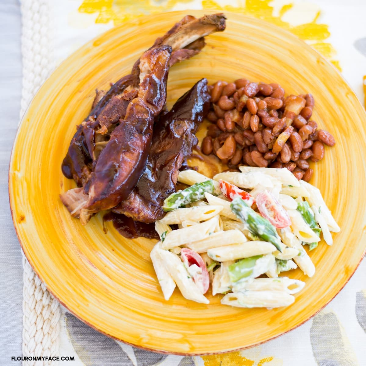 Smoky BBQ Spare ribs served with a side of baked beans and a pasta salad on a yellow glass plate.