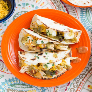 Chicken salsa served on warm tortilla with toppings on an orange plate