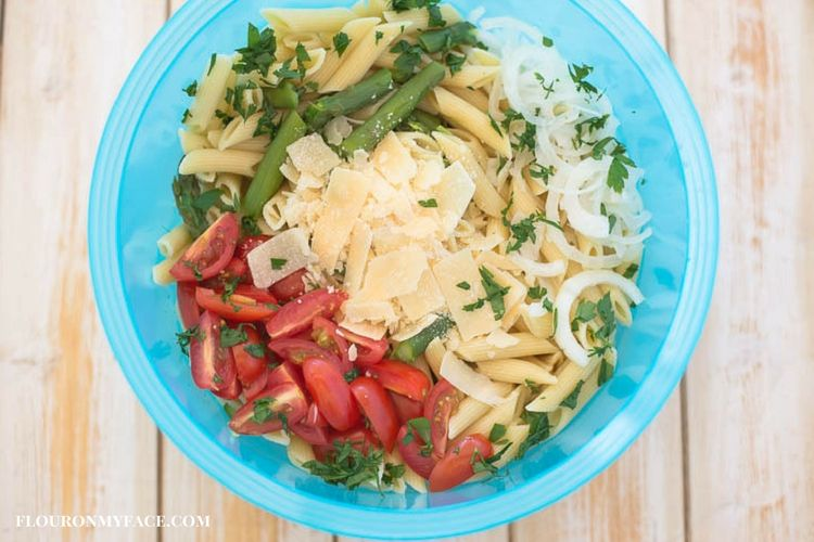 Fresh summer vegetables and Parmesan cheese are delicious in this Aspapragus Tomato Pasta Salad recipe.