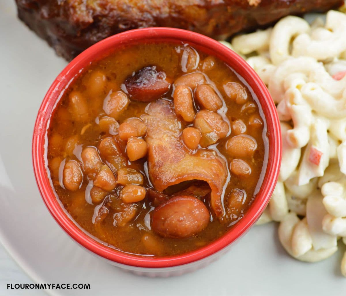 Overhead image of a small red bowl of baked beans.