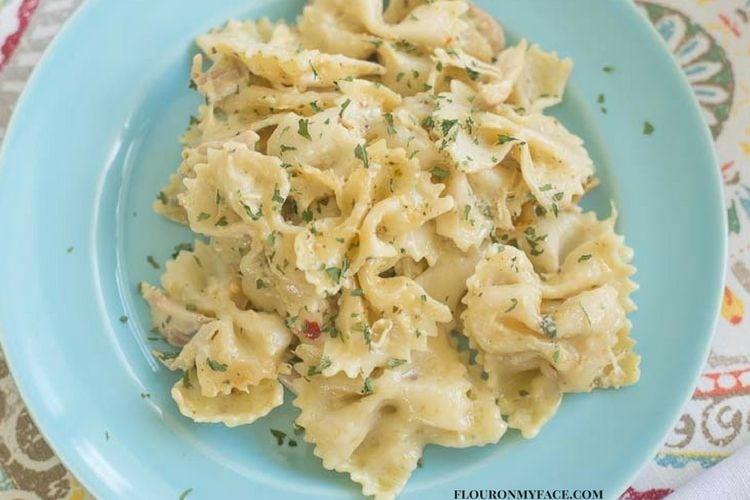 Crock Pot Chicken Alfredo Pasta Casserole recipe on a blue plate via flouronmyface.com