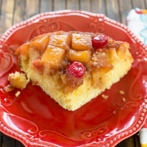 A slice of Crock Pot Pineapple Upside Down Cake on a red dessert plate